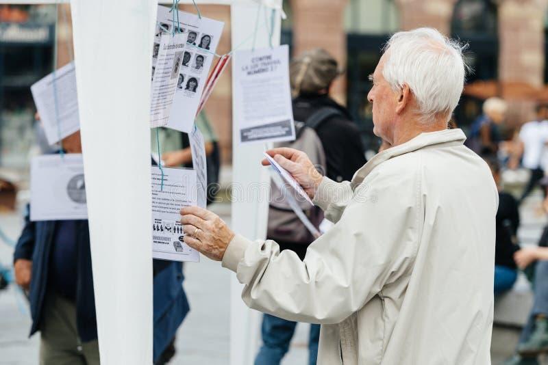 Starszego mężczyzna czytanie oczywisty przeciw Macron fotografia stock