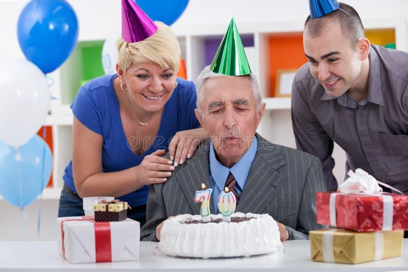 Starszego mężczyzna dmuchanie w świeczkach na torcie obraz stock