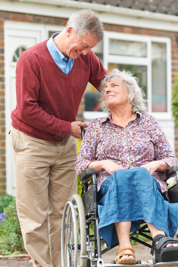 Starszego mężczyzna dosunięcia Niepełnosprawna żona W wózku inwalidzkim obrazy royalty free
