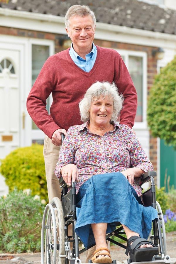 Starszego mężczyzna dosunięcia Niepełnosprawna żona W wózku inwalidzkim obrazy stock