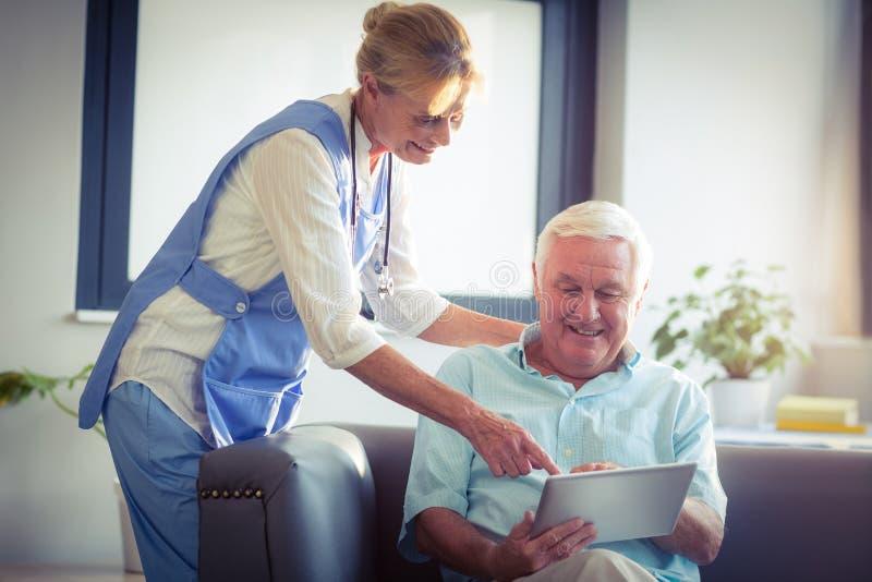 Starszego mężczyzna i kobiety lekarka używa cyfrową pastylkę obrazy royalty free