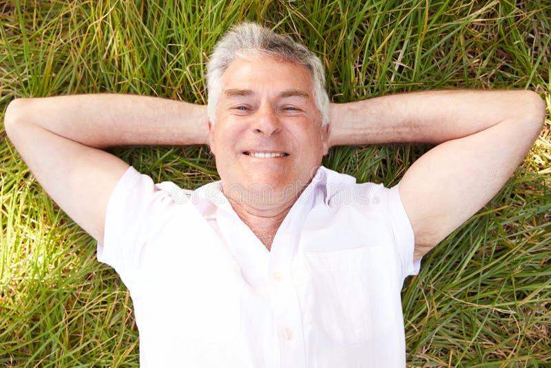 Starszego mężczyzna lying on the beach na trawy relaksować zdjęcia stock