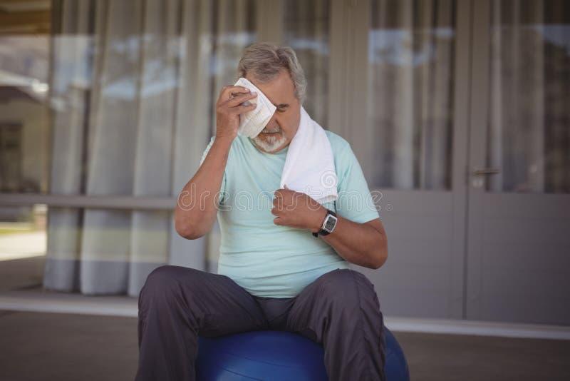 Starszego mężczyzna obcierania pot z jego twarzy z ręcznikiem zdjęcie stock