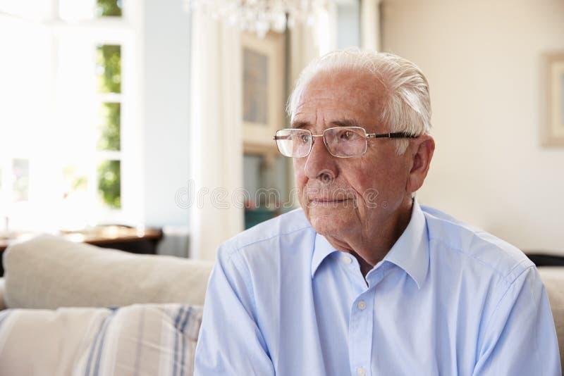 Starszego mężczyzna obsiadanie Na kanapie Cierpi Od depresji W Domu zdjęcie royalty free