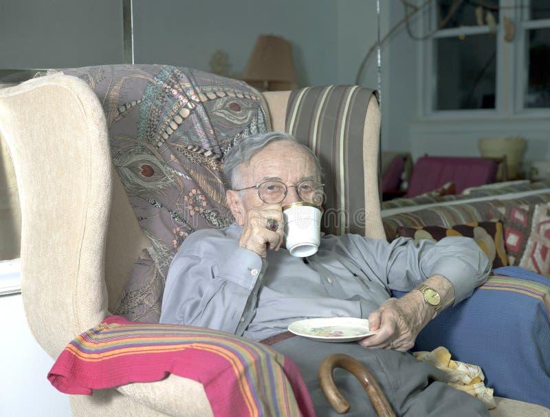Starszego mężczyzna obsiadanie na leżance z filiżanki pić zdjęcie stock