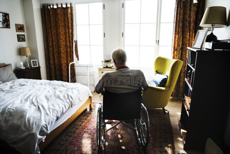 Starszego mężczyzna obsiadanie na wózku inwalidzkim samotnie zdjęcie royalty free