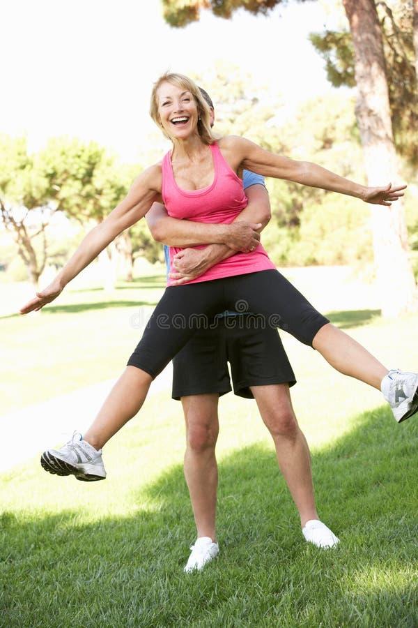 Starszego Mężczyzna Podnośna Kobieta Podczas Ćwiczenia W Parku zdjęcie stock