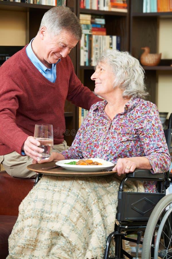 Starszego mężczyzna porci żona W wózku inwalidzkim Z posiłkiem fotografia stock