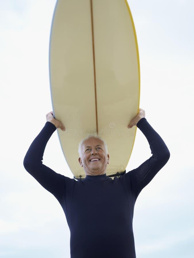 Starszego mężczyzna przewożenia Surfboard koszt stały obraz royalty free