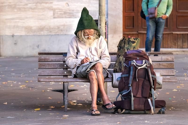 Starszego mężczyzny backpacker obsiadanie na kwadratowej ławce, pisze puszek notatkach na notepad jest ubranym eyeglasses i gnom  zdjęcia stock