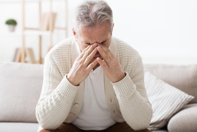 Starszego mężczyzny cierpienie od migreny, siedzi na kanapie zdjęcie stock
