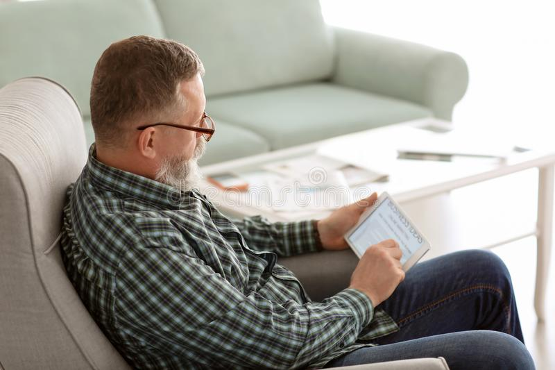 Starszego mężczyzny czytelnicza wiadomość na pastylka ekranie w domu obraz stock