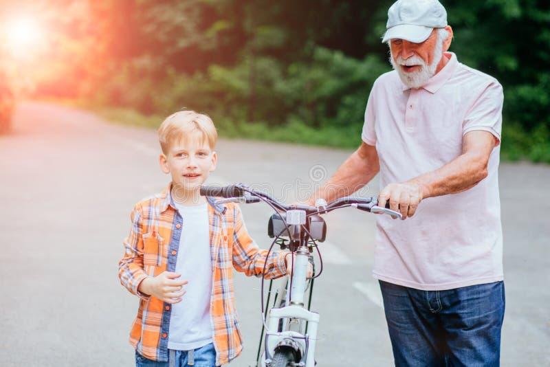 Starszego mężczyzny dziad i wnuk opowiada podczas gdy chodzący z bicyklem w parku Rodzina, pokolenie, bezpieczeństwo i ludzie poj zdjęcia royalty free