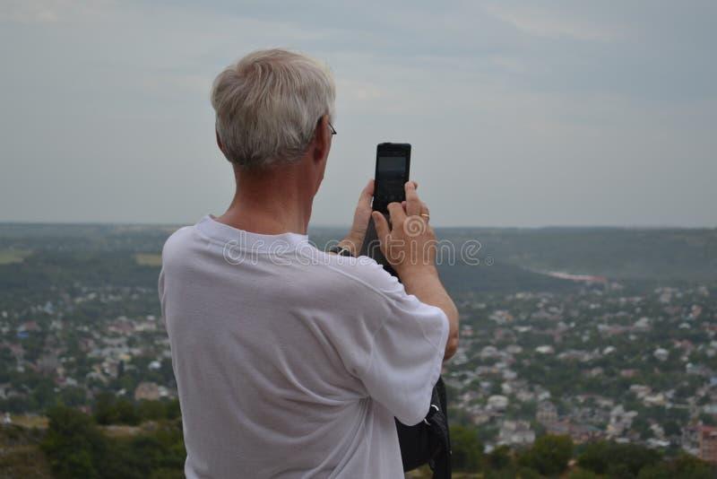Starszego mężczyzny fotografie na telefonie widok miasto Pyatigorsk, Rosja obraz stock