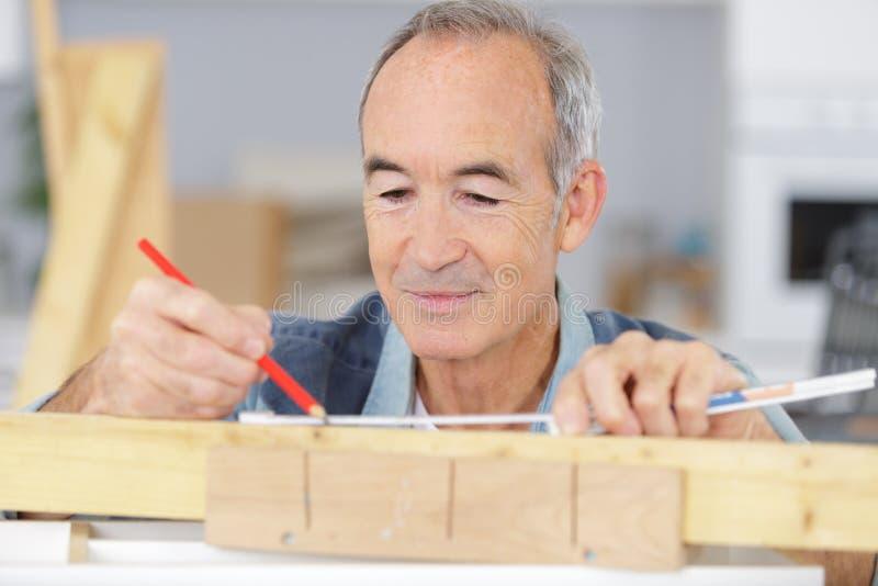 Starszego mężczyzny ocechowania pozycja na drewnie obraz stock