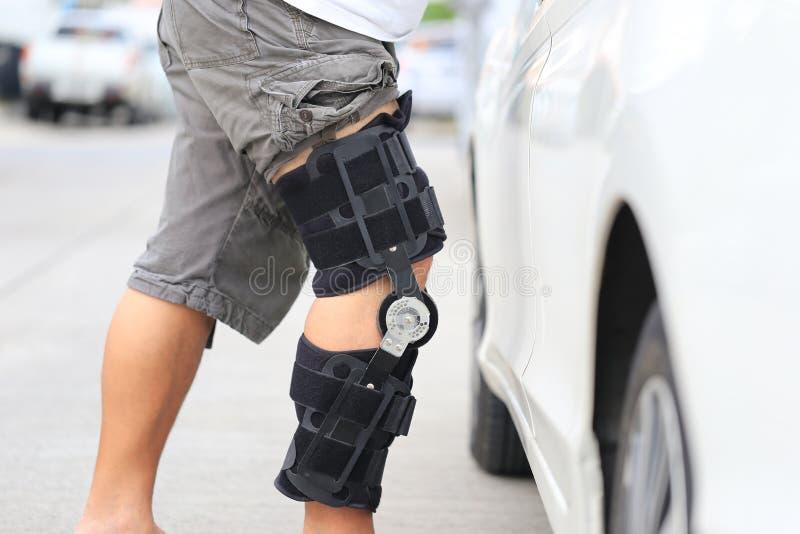 Starszego m??czyzny odzie?y poparcia kolanowy bras na nogi pozycji przy samochodowym parking, poj?ciem, Medycznego i opieki zdrow obraz royalty free