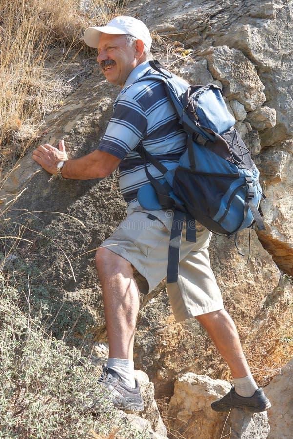 Starszego mężczyzny pięcie na skale obraz stock