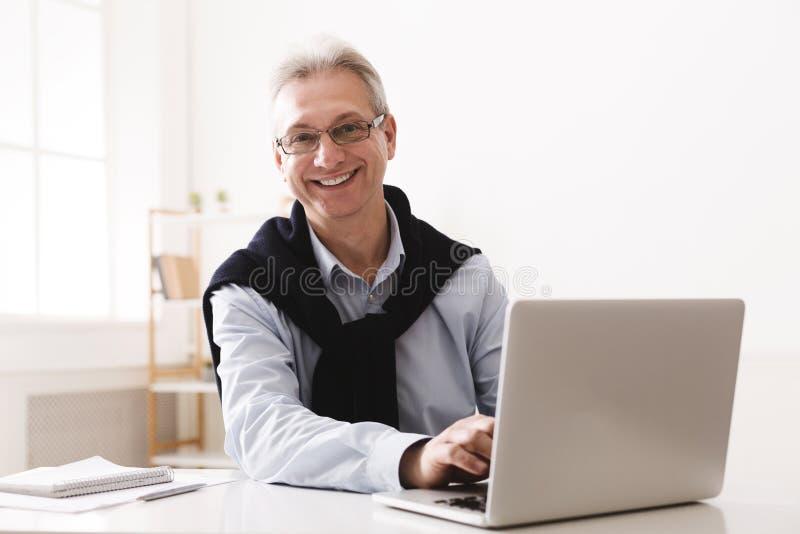 Starszego mężczyzny używać komputerowy i patrzeć kamerę obrazy royalty free