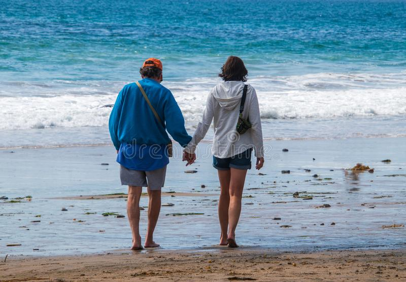 Starszego obywatela dziecko wyżu demograficznego samiec i żeński caucasian pary odprowadzenie na plaży w kierunku oceanu mienia r obrazy royalty free
