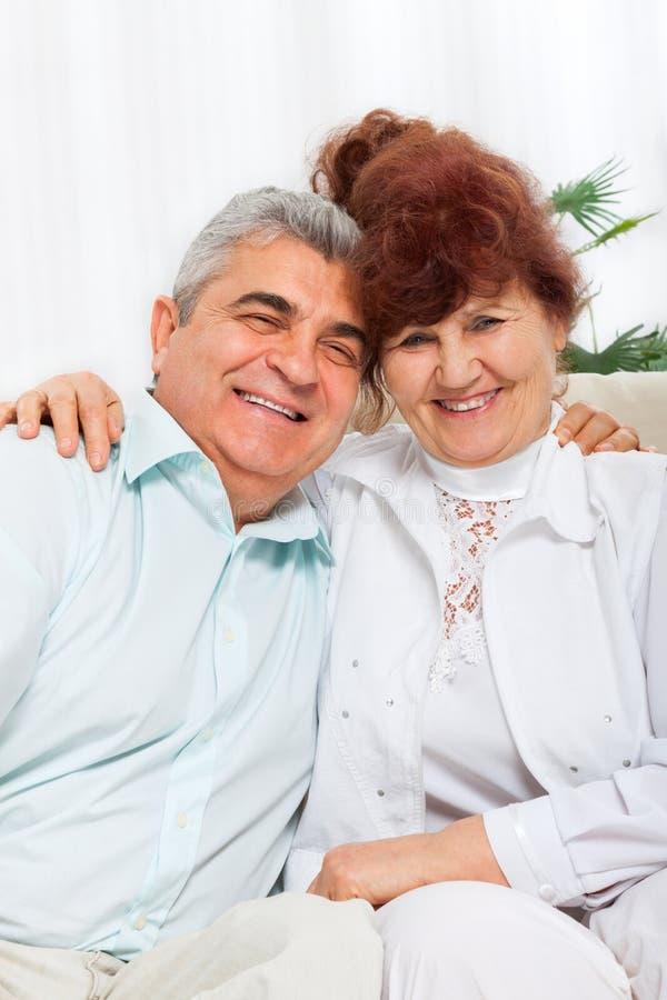 Starszego para uśmiechu szczęśliwego uścisku siedząca kanapa fotografia stock