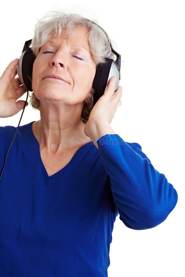 starszego słuchania zrelaksowana kobieta obrazy royalty free