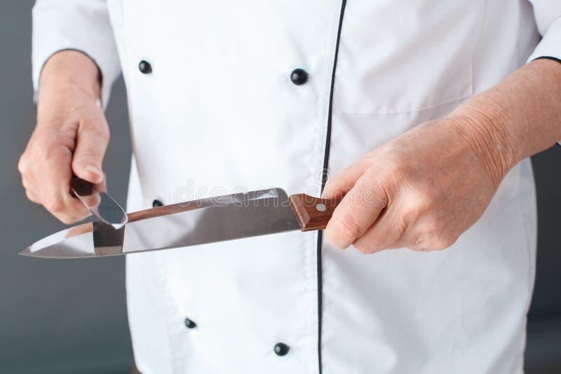 Starszego szefa kuchni pracowniana pozycja odizolowywająca na szarych ostrzenie nożach w górę obraz stock