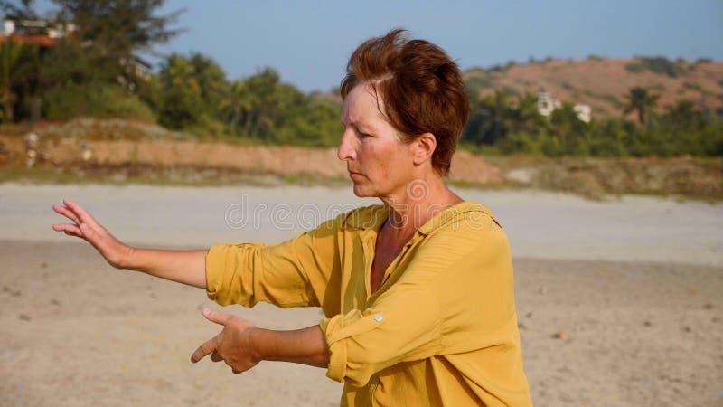 Starszej kobiety ćwiczy taiji gimnastyczny przy piaskowatą plażą zdjęcia royalty free