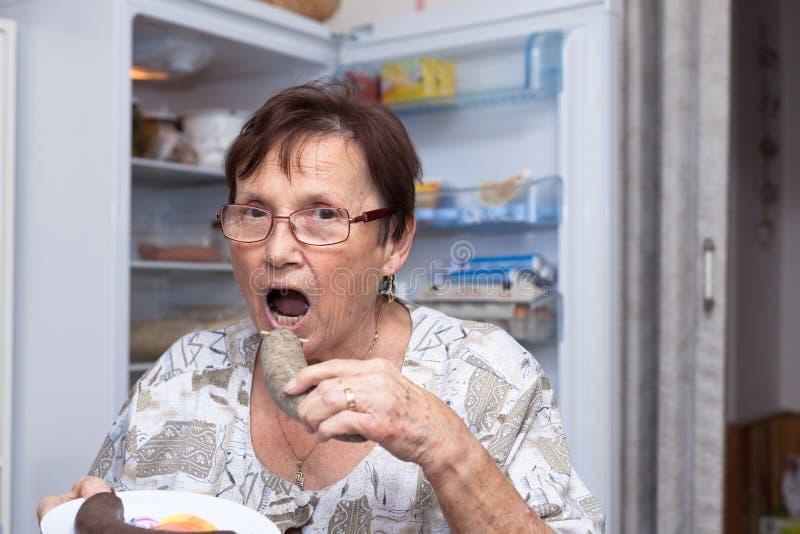 Starszej kobiety łasowania wieprzowiny wątrobowa kiełbasa obraz stock