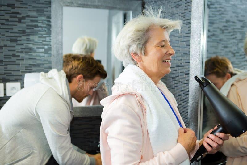 Starszej kobiety blowdrying w?osy w gym washroom zdjęcie stock