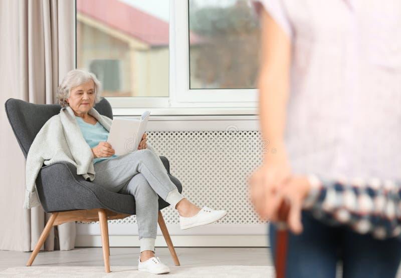 Starszej kobiety czytelnicza książka blisko okno w domu zdjęcie royalty free