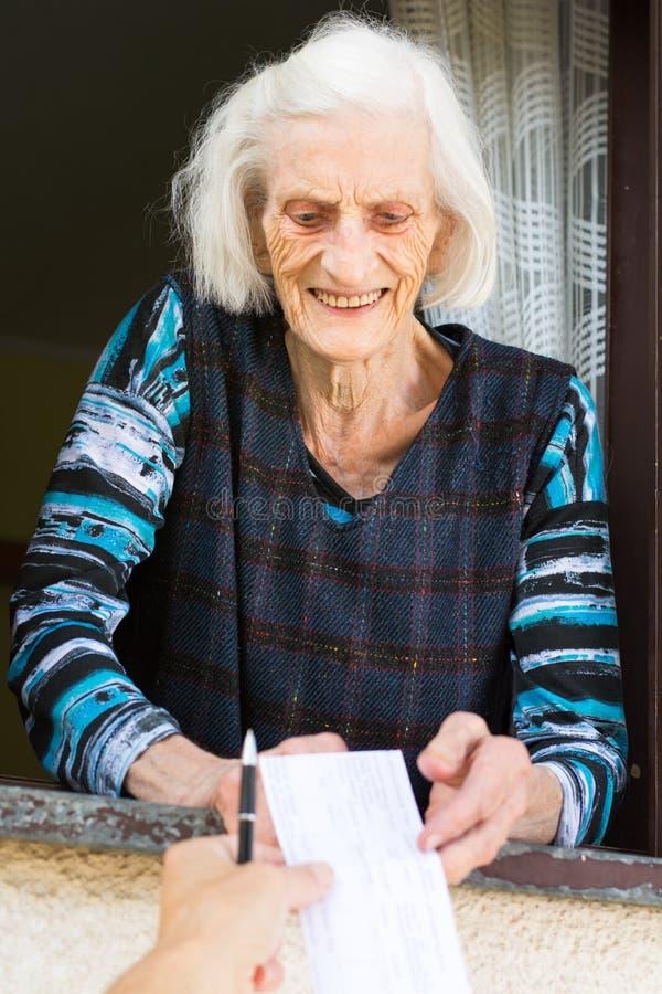 Starszej kobiety emerytura odbiorczy czek w domu obrazy stock