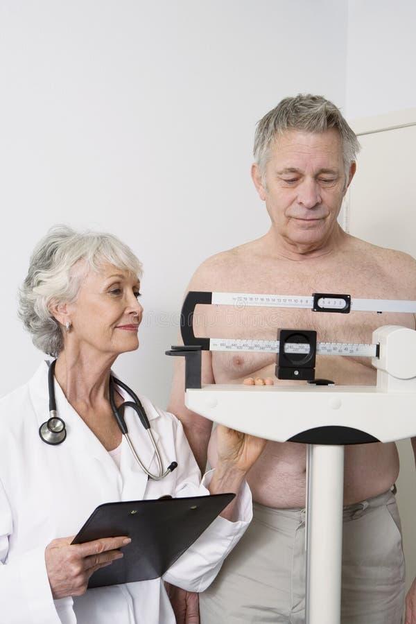 Starszej kobiety lekarki pacjenta Pomiarowy ciężar obrazy stock