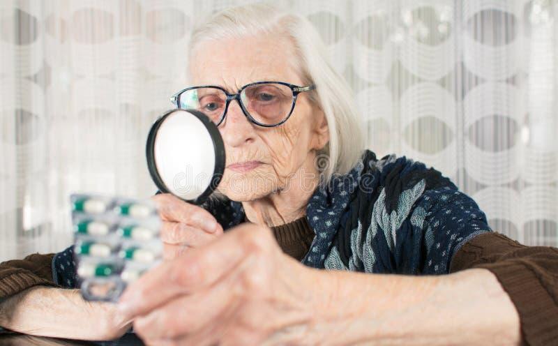 Starszej kobiety pigułki czytelniczy imię z powiększać - szkło zdjęcie stock