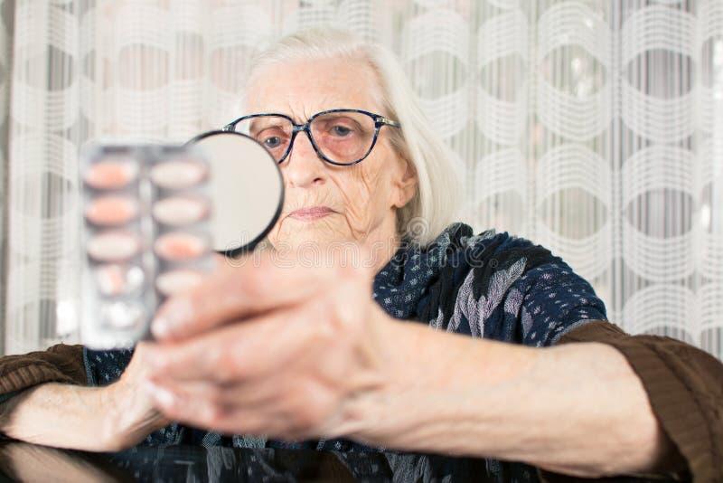 Starszej kobiety pigułki czytelniczy imię z powiększać - szkło zdjęcie royalty free