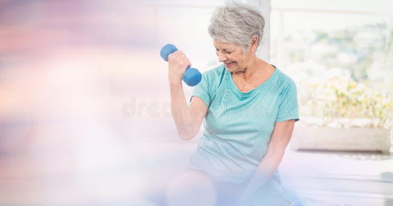 Starszej kobiety podnośni dumbbells w gym fotografia stock