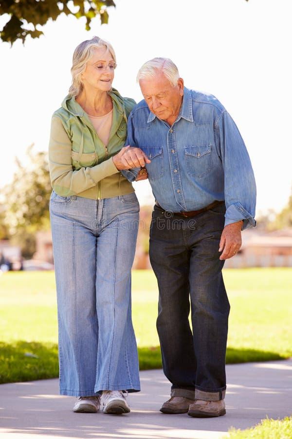 Starszej kobiety Pomaga mąż Gdy Chodzą W parku Wpólnie obrazy royalty free