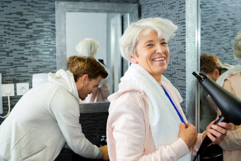 Starszej kobiety suszarniczy włosy z włosianą suszarką fotografia stock