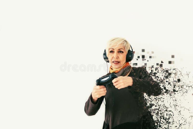 Starszej osoby kobieta bawić się wideo grę i rozpada się w piksle Konceptualna fotografia z wizualnych skutków znaczyć zdjęcia stock