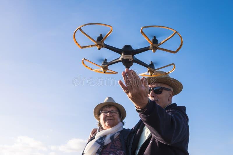 Starszej osoby para bawić się z latającym trutniem obraz stock