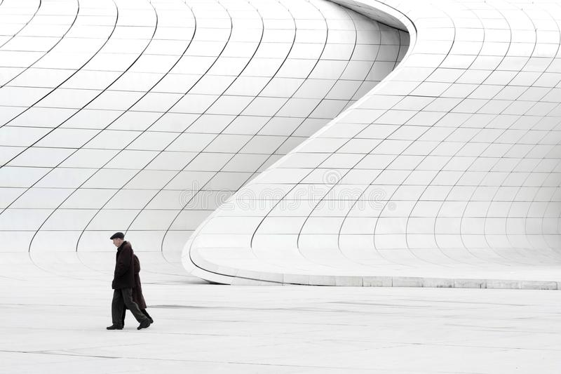 Starszej osoby para chodzi blisko nowożytnych budynków obraz stock
