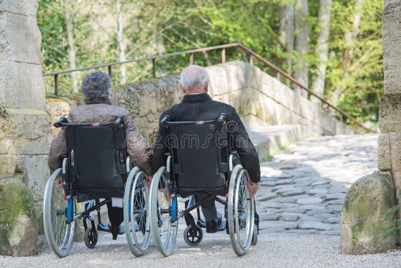Starszej osoby para na ich wózku inwalidzkim zdjęcie royalty free