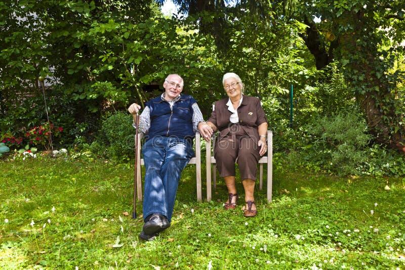 Starszej osoby para siedzi ręka w rękę obraz stock