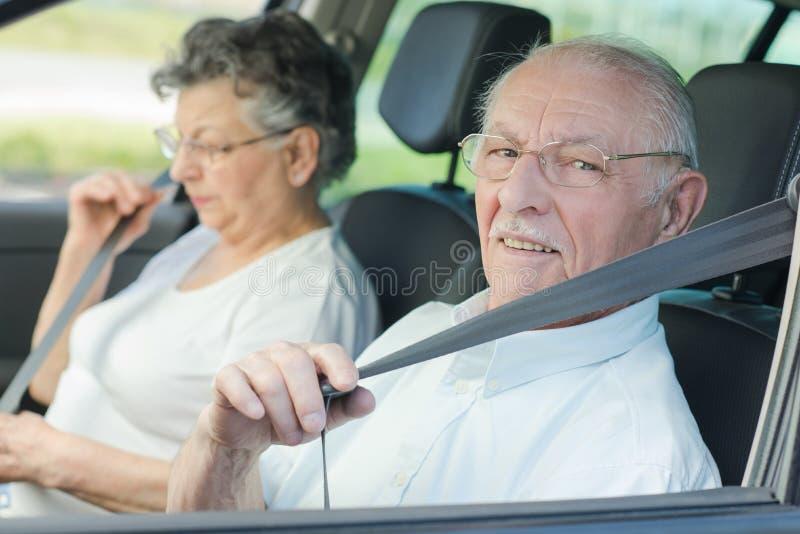 Starszej osoby pary kładzenie na ich seatbelts fotografia royalty free