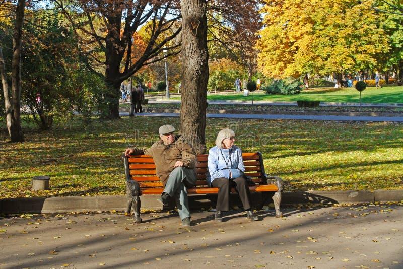 Starszej osoby pary obsiadanie na ławce w jesień parku Gorkogo w Moskwa obraz royalty free