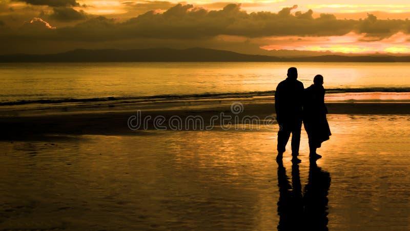 Starszej osoby pary odprowadzenie na plaży W zmierzchu zdjęcia royalty free