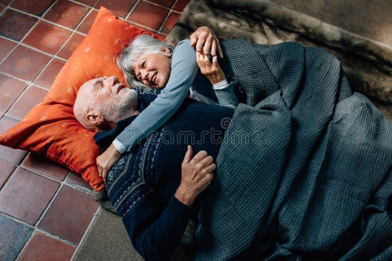 Starszej pary łgarski puszek na podłodze trzyma each opowiadać i inny Starego człowieka i kobiety dosypianie na podłodze zakrywa  obrazy royalty free