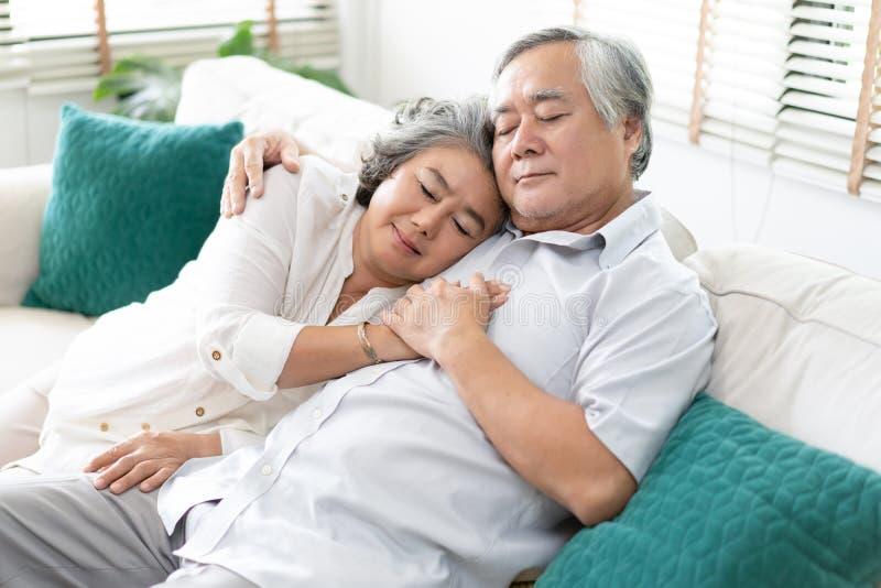 Starszej pary relaksujący dosypianie wpólnie w domu na kanapie w żywym pokoju Relaksuje i styl życia pojęcie fotografia stock