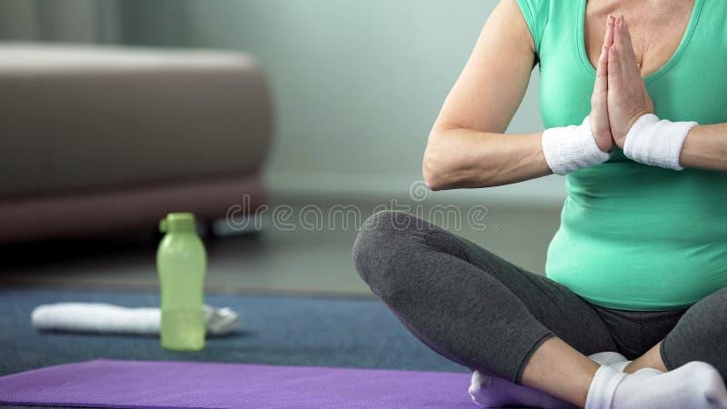Starszej sport damy joga ćwiczy pozy w domu, duchowa praktyka, trenuje obraz royalty free