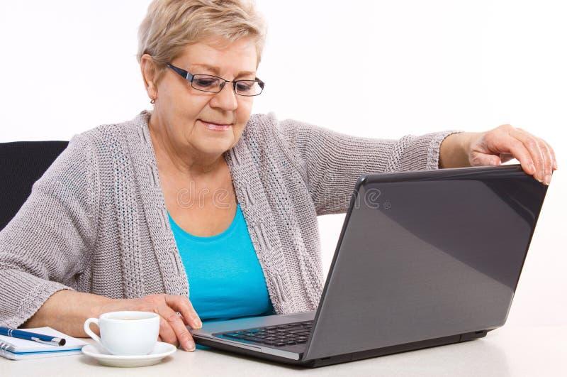 Starszej starszej kobiety końcowy laptop na stole w domu zdjęcia stock