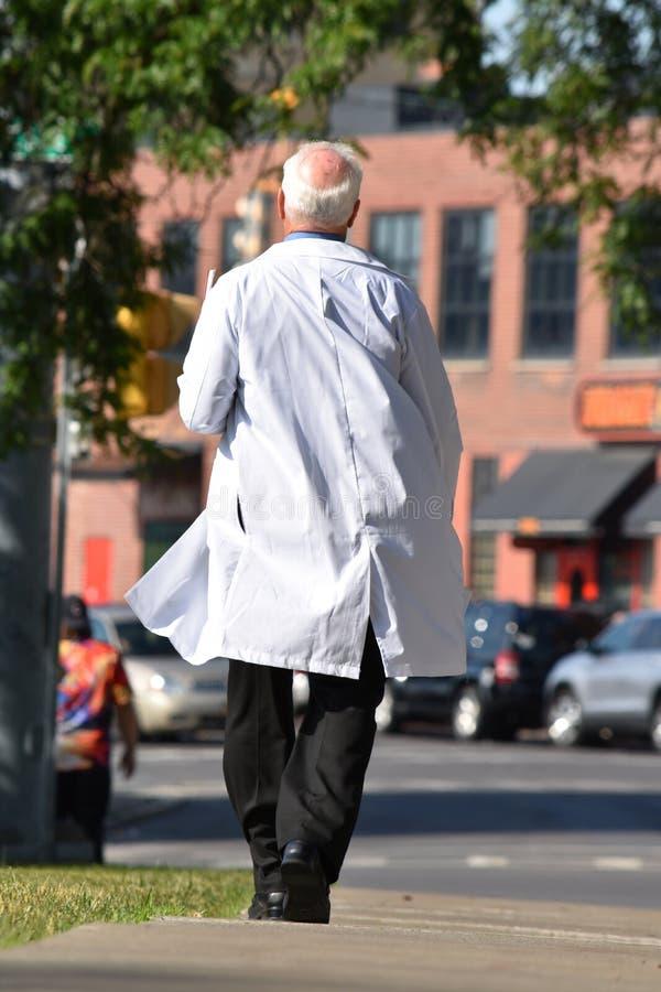Starszy łysienie samiec lekarki odprowadzenie Na chodniczku zdjęcia stock